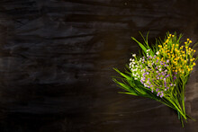 Wildflowers On A Black Wooden Or Metal Background