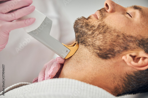Fotografia Good-looking young man undergoing laser hair removal procedure