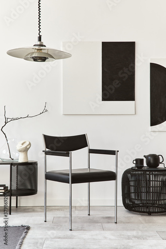 Fototapeta Interior design of modern living room with black stylish commode, chair, mock up art paintings, lamp, pouf, decorations and elegant accessories in home decor. Template. obraz