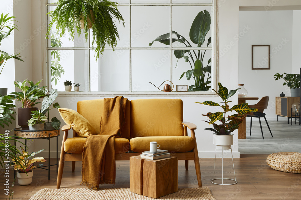 Fototapeta Interior design of scandinavian open space with yellow velvet sofa, plants, furniture, book, wooden cube and personal accessories in stylish home staging. Template.