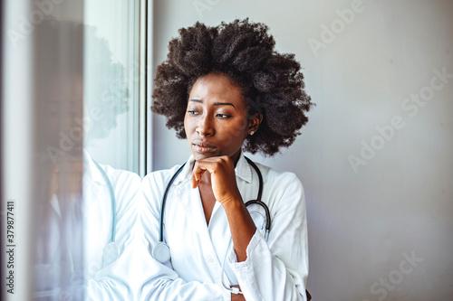 Female doctor with head pain standing near window Canvas-taulu