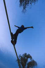 Silhouette Of Man Keeping Balance On Slackline Outdoor During Tw