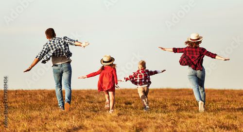 Happy family: mother, father, children son and daughter running on autumn sunset.