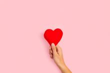 Mano Femenina Sosteniendo Un Corazón Sobre Un Fondo Rosa Pastel Liso Y Aislado. Vista De Frente. Copy Space
