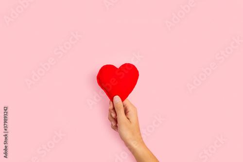 Photo Mano femenina sosteniendo un corazón sobre un fondo rosa pastel liso y aislado