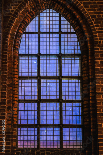 Faint, blue light coming from a church 's Gothic window conveys a celestial, deep feeling with profund, intense and abyssal concept Canvas Print