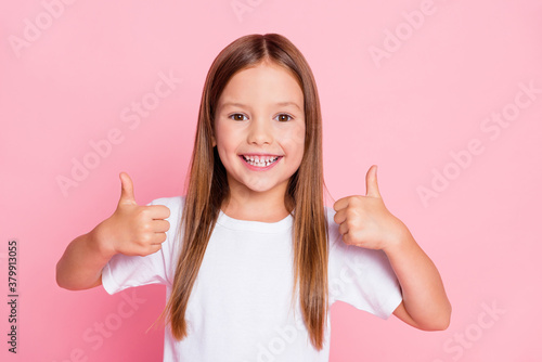 Fototapeta Photo of positive cheerful kid girl show thumb up sign enjoy new school ads adverts wear white clothes isolated over pastel color background obraz