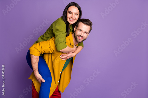 Fototapeta Profile photo pretty lady handsome guy couple carry piggyback meet adventures playful mood spend time quarantine wear casual bright shirts pants outfit isolated purple color background obraz