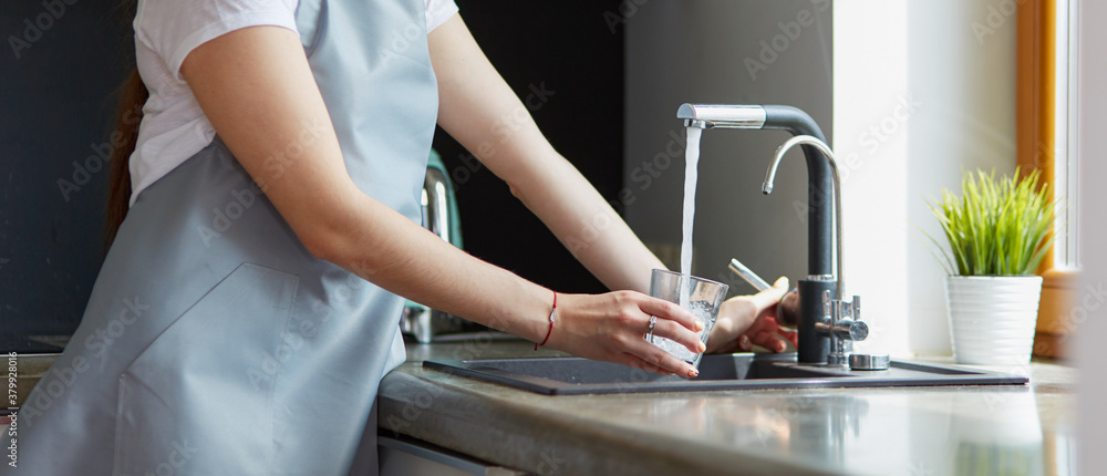 Fototapeta Human hand holding glass pouring fresh drink water at kitchen faucet