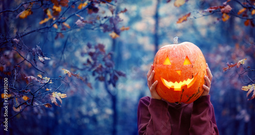 Boy holding carved pumpkin for halloween in front of his head in dark autumn forest. Halloween holiday concept.
