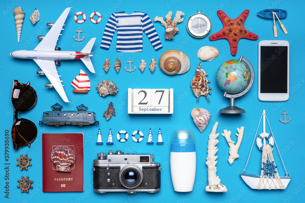 Fototapeta Happy world tourism day. Touristic objects, smart phone, passport, photo camera, sunglasses and decorative items on blue background. Flat lay, top view. Calendar date September 27, world tourism day