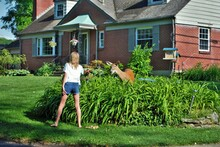 Young Girl With A Doe Deer Walking Through A Residential Neighborhood