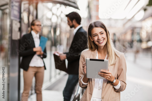 Young happy businesswoman holding digital tablet outside of modern building, businesspeople in background.