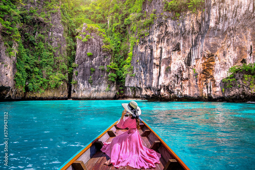 Fotografía Beautiful girl sitting on the boat and looking to mountains in Phi phi island, Thailand