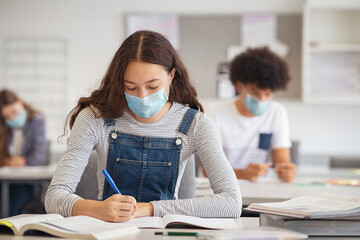 Fototapeta Boks High school girl studying in class with face mask