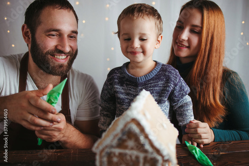 Fototapeta Family decorating Christmas gingerbread house obraz