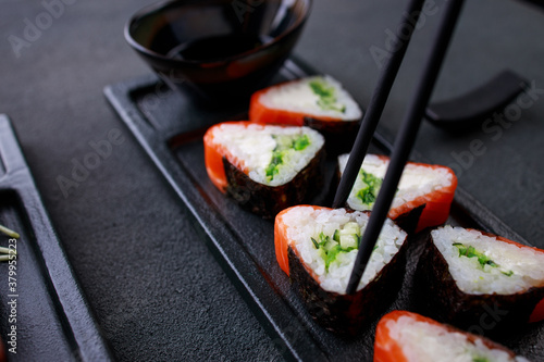Fototapeta Chopsticks taking salmon maki roll from plate obraz
