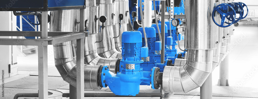 Obraz Modern industrial boiler room with pumps and pipe lines supplying steam with pressure gauges installed in. Blue toning. Panoramic banner. fototapeta, plakat