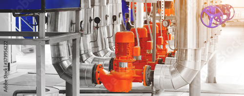Modern industrial boiler room with pumps and pipe lines supplying steam with pressure gauges installed in with sunflare Fototapet