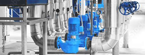 Fototapeta Modern industrial boiler room with pumps and pipe lines supplying steam with pressure gauges installed in. Blue toning. Panoramic banner. obraz