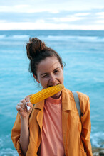 Young Woman Enjoying Grilled Corn On The Ocean Background