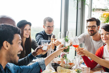 Group Of Mixed Race Friends Having Fun And Clinking Glasses During Restaurant Lunch