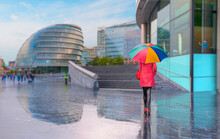 Woman In Red Clothes With Colorful Umbrella Walking On The Road - Blured London City Hall Bulding With Reflection After Rain On The Bank Of The River Thames - London , United Kingdom
