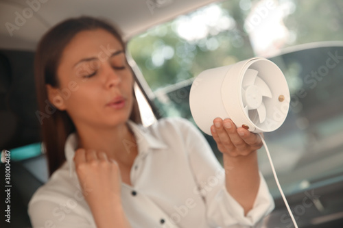 Fotomural Young woman with portable fan suffering from heat in car on summer day
