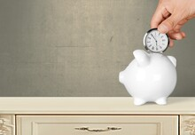 Hand Depositing Clock In Piggy...