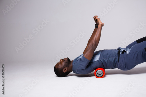 Photo A man is doing exercises on a foam roller on his back
