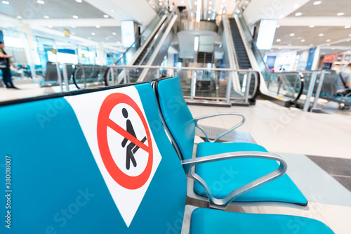 Fototapeta Signs on the seats at the airport draw the line between safe and dangerous areas for Seating to comply with safe social distance