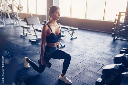 Photo Beautiful girl doing lunges exercise with dumbbells in gym.