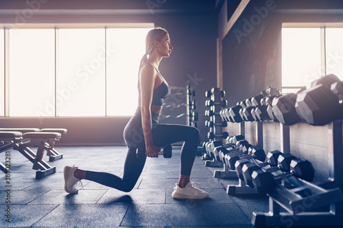 Fotografie, Tablou Beautiful girl doing lunges exercise with dumbbells in gym.