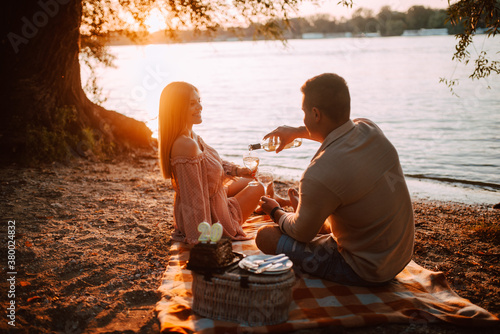 Fototapeta A beautiful blonde caucasian woman and a man are sitting on the beach drinking wine. A loving couple on a picnic by the river obraz