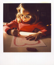 Polaroid Image Of A Cute Girl Coloring A Heart In Morning Sunlight While Wearing Sunglasses