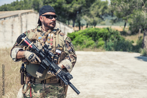 Navy SEALs fighter in ballistic goggles, equipped military ammunition and body armour, holding service rifle, looking in camera while standing outdoors Fototapet