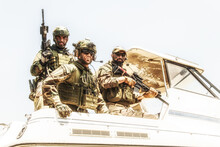 Army Special Operations Soldiers, SEALs Team, Elite Commando Fighters Group Loaded With Ammunition, Wearing Helmets And Radio Headset, Armed Assault Rifles, Standing Together On Speed Boat Stern