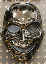 Metallic Sinister Ghost Mask Isolated Against Pegboard Wall
