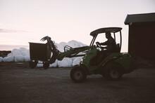 Rancher Driving Forklift At Farm During Dusk