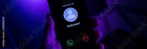 Fotografía Homem segurando celular recebendo chamada desconhecida - Fundo com a tela do com