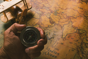 Hand hold old compass discovery and wooden plane on vintage paper antique world map background, Retro style cartography travel geography navigation