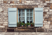 Mediterranean Window With Wooden Shutters And Flower Pots