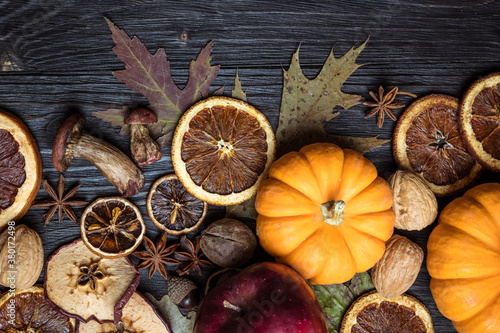 Obraz na plátně Autumn background with dried fruits, oranges, apples, nuts, anise, mushrooms, acorns and pumpkin