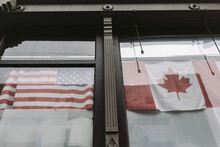 Canadian And American Flags Hanging Together