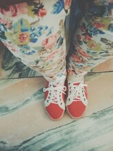 Young Woman Wearing Red Shoes And Flowery Jeans