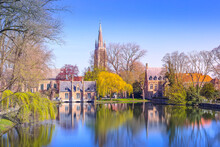Minnewater Lake Panorama, Reflection Of Gothic Flemish Style House, Blue Sky, Spring Trees In Bruges, Belgium