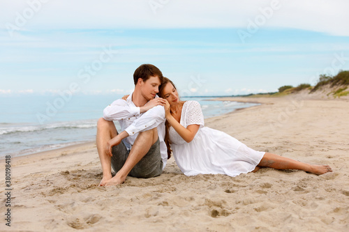 Fototapeta Young couple of lovers enjoy the good weather on the sandy beach