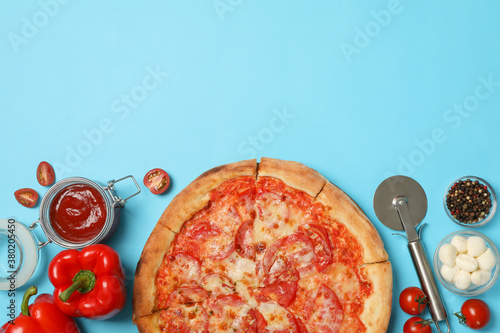 Fotografiet Tasty pizza and ingredients on blue background