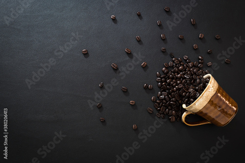 Obraz na plátně cup of coffee beans fell on the table top view