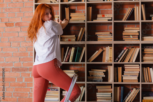 Redhead female college student taking book from shelf in library Fototapet